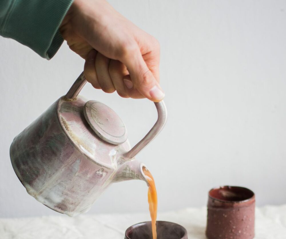 Woman pouring tea from kettle into the cup