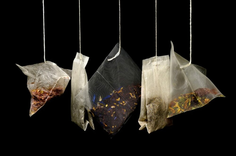 Different tea bags hanging infront of a black background