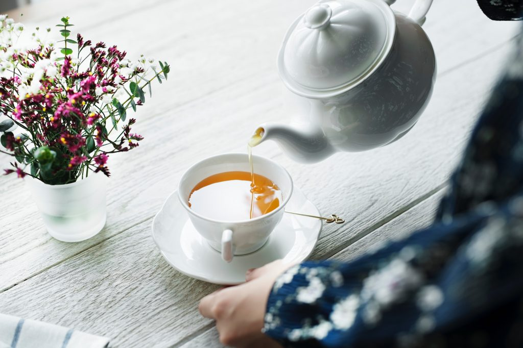 Organic tea being poured from a tea pot into a white teacup