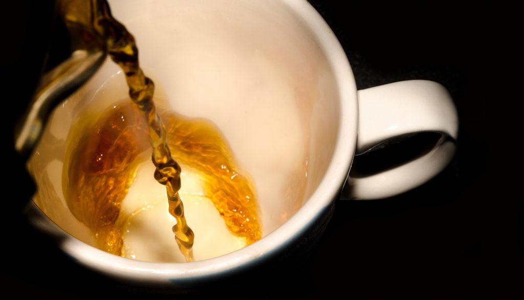 Pouring black tea into a white cup