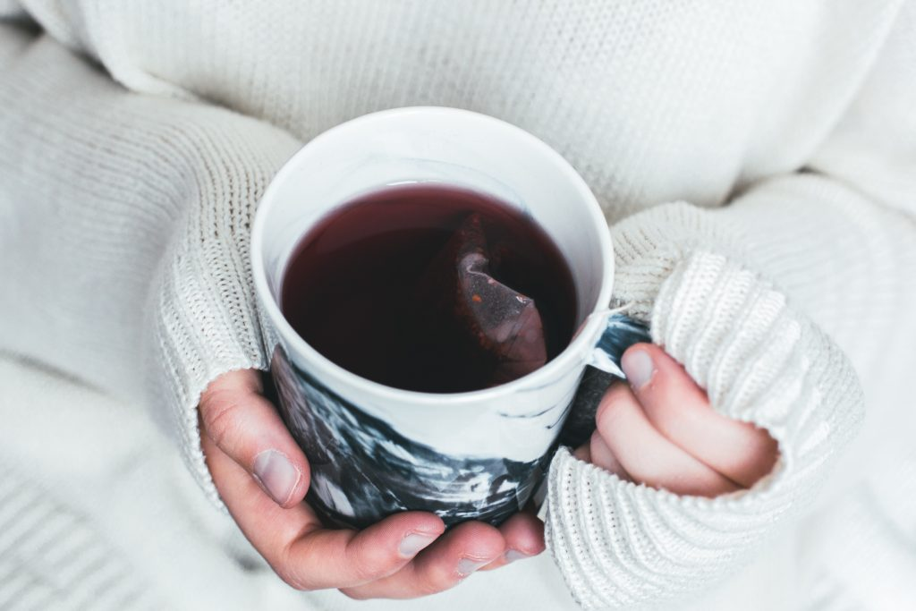 Woman in a white sweater holding a cup of tea with a tea bag in it