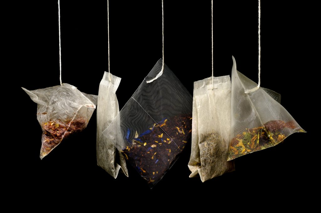 5 teabags hanging against a black background