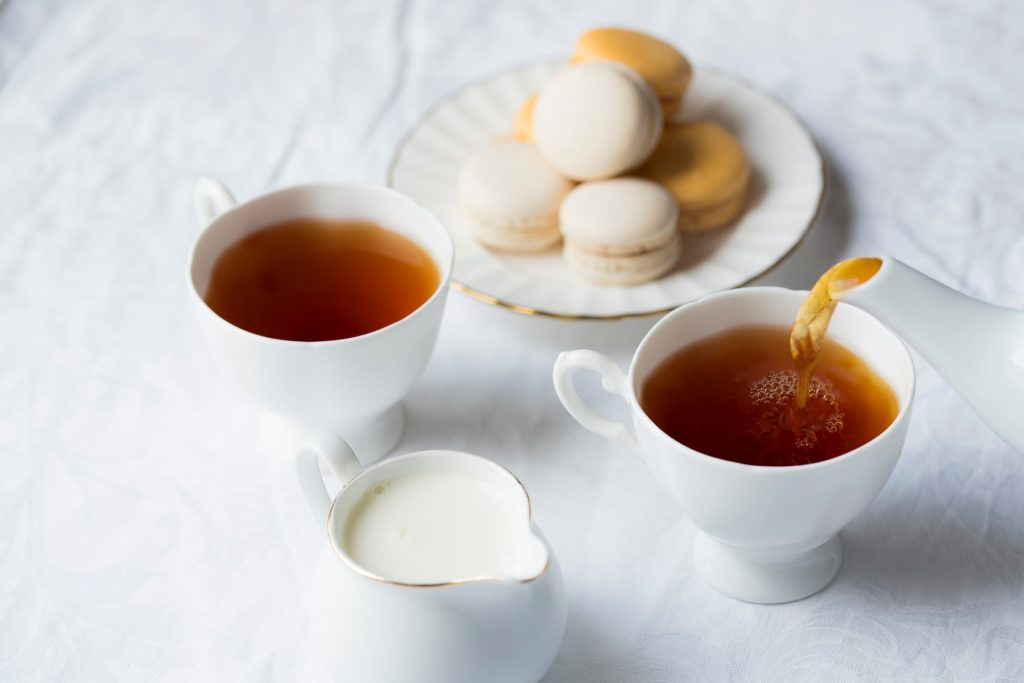 Hot tea served with cream and French macarons