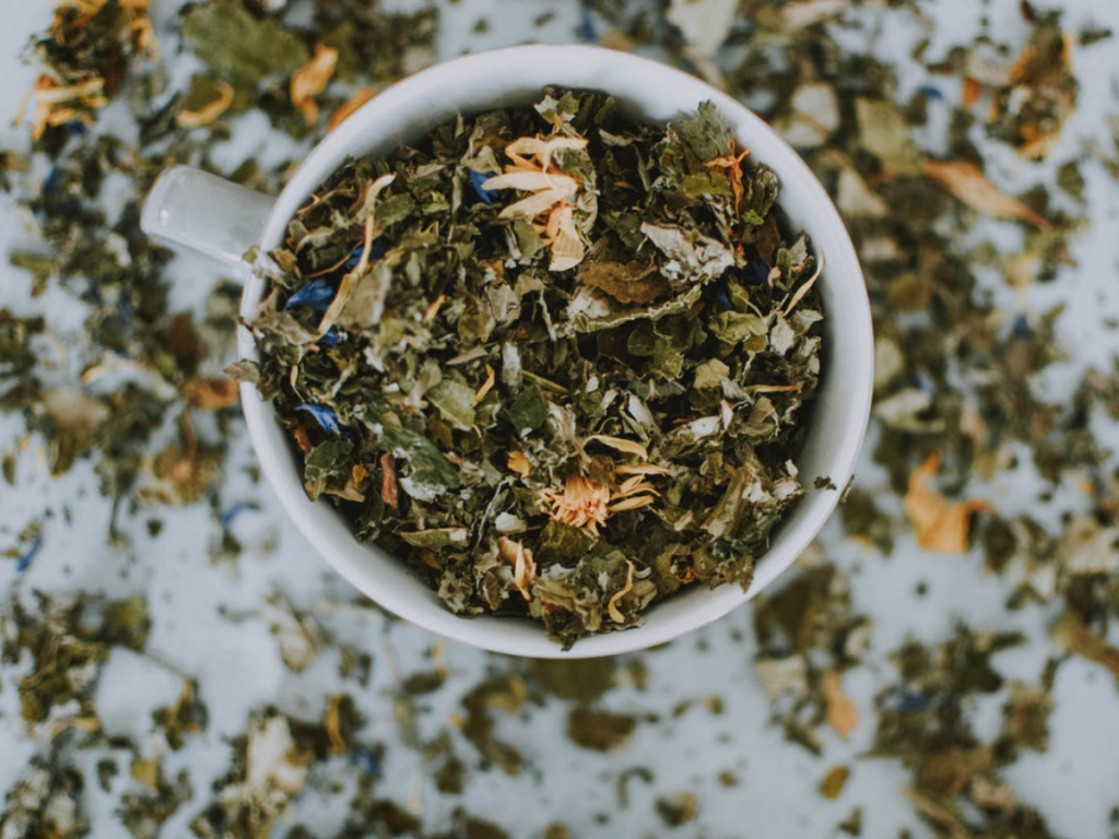 Close photo of dried tea leaves in a white cup