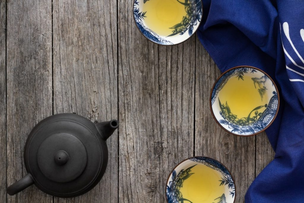 Black teapot surrounded by cups of tea
