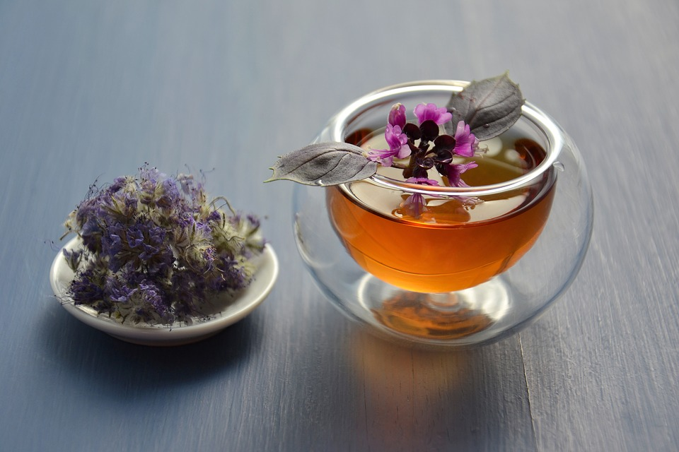 A small clear bowl of tea flavored with flowers