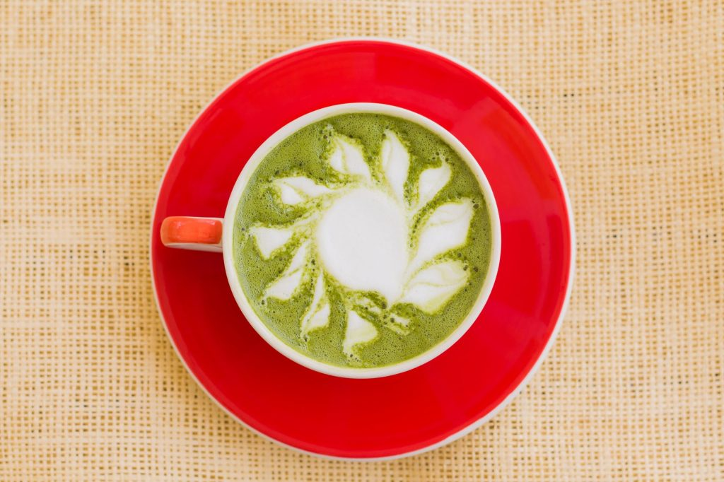 A cup of matcha latte placed over a red saucer