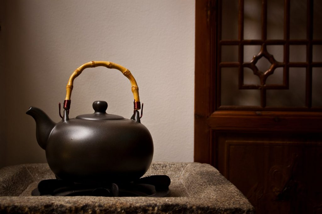 A brown tea kettle with wooden handle on stove