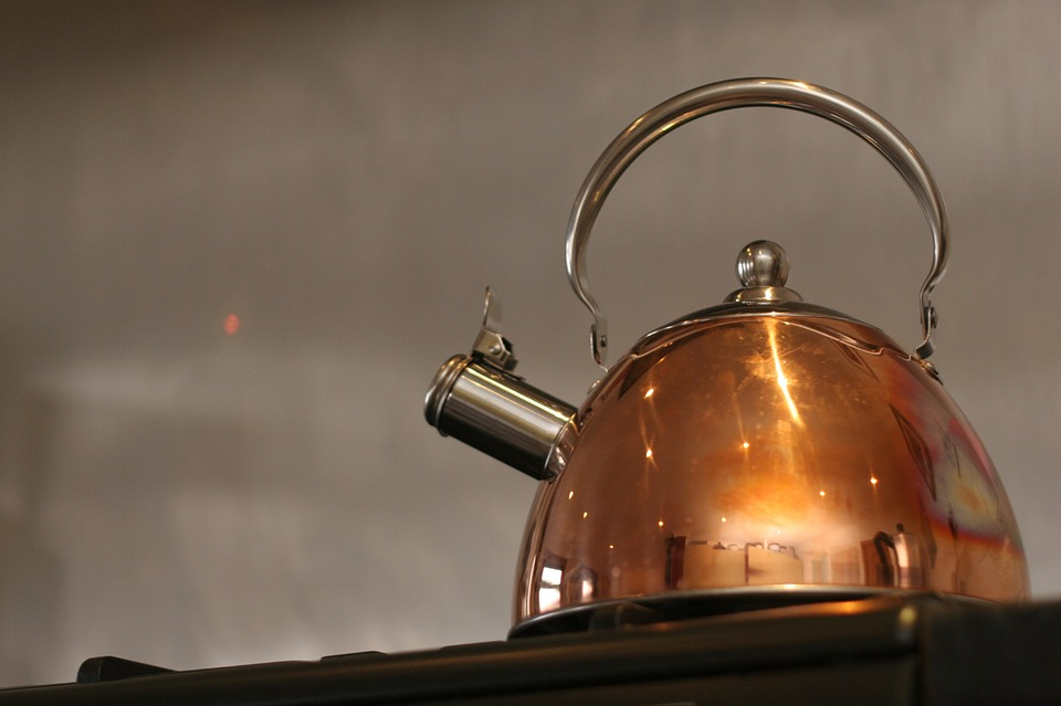 A whistling tea kettle on a  stove