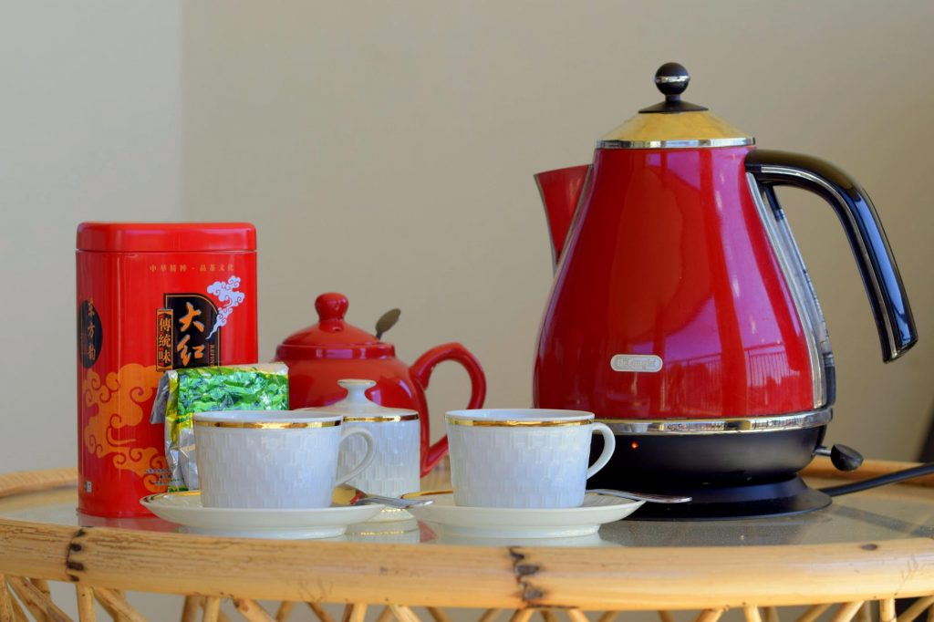 A red electric tea kettle and a tea set on a table