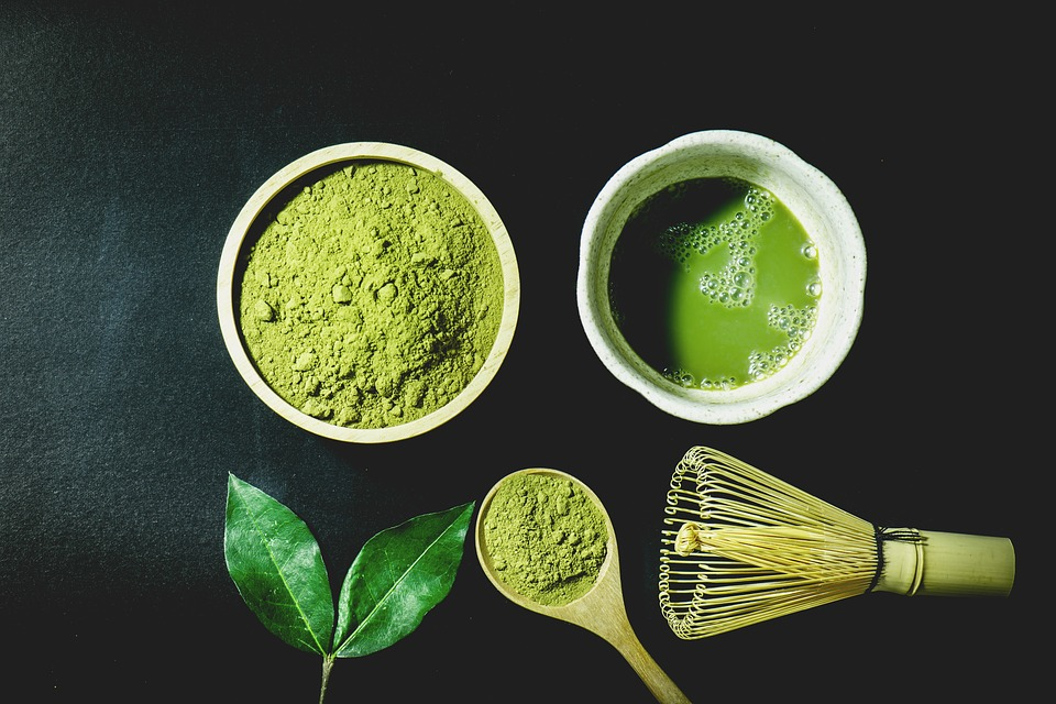 A cup of matcha tea near a bowl of powder, whisker and wooden spoon