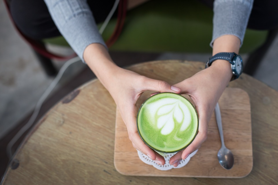 A lady holding a cup of frothy matcha