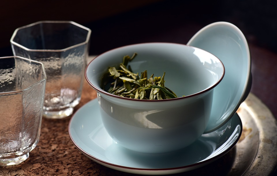 A cup of green tea leaves beside two empty glasses