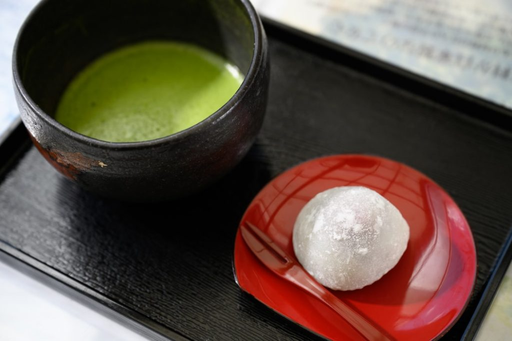 A bowl of matcha tea paired with a dessert