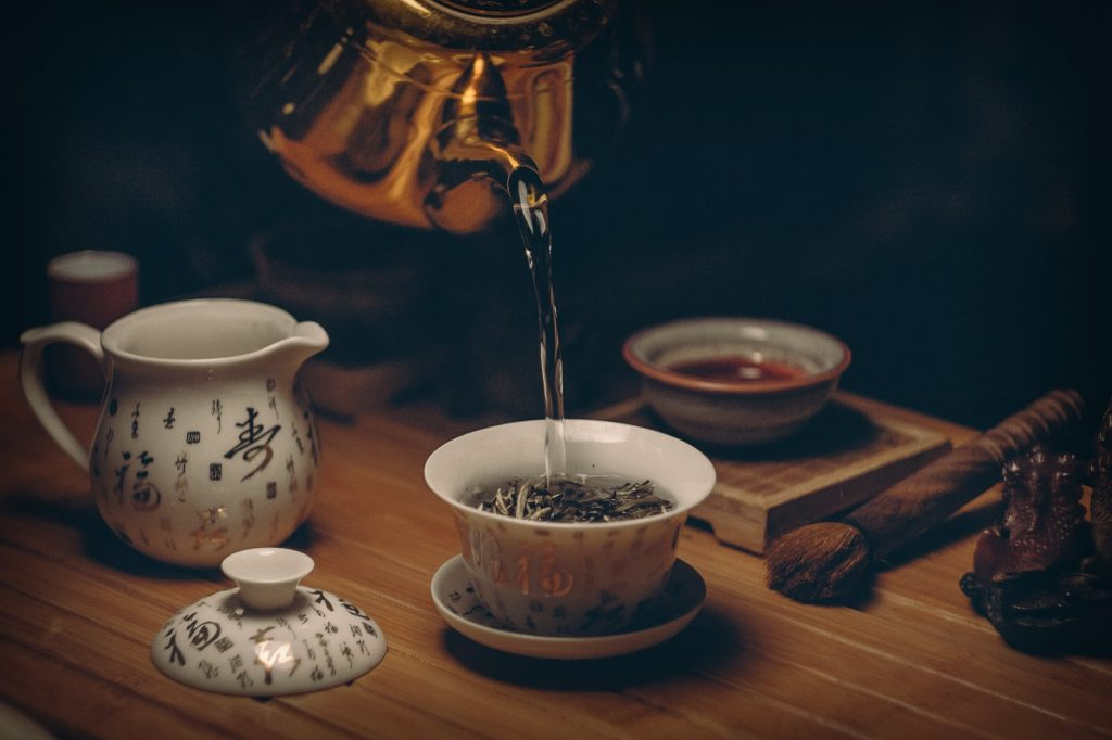 Japanese stainless teapot brewing loose tea leaves in a white cup