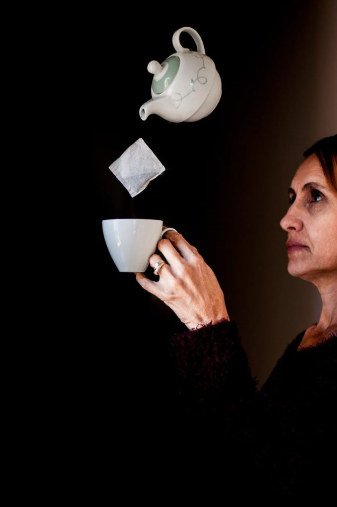 Woman holding a teacup with a teabag and a teapot in mid air