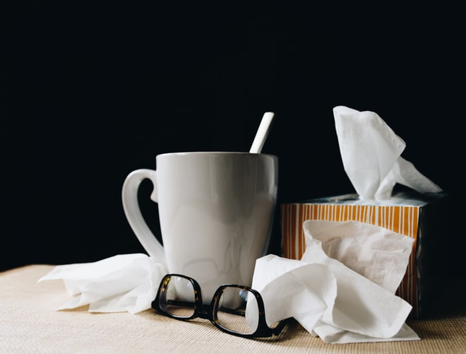 A mug of hot tea with used tissues and glasses scattered around it