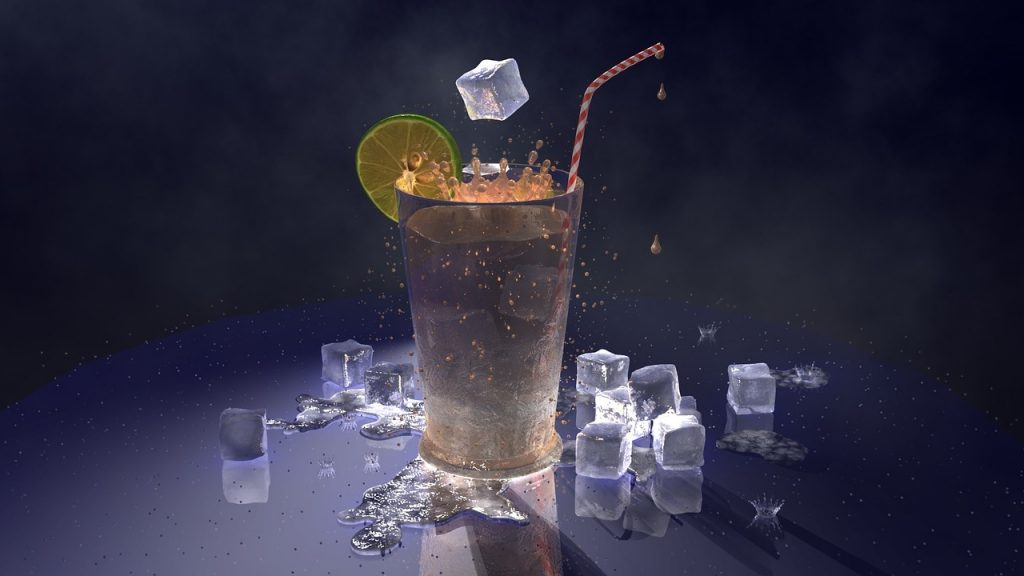 A few ice cubes are placed around a glass of iced tea while an ice cube is being added to the glass