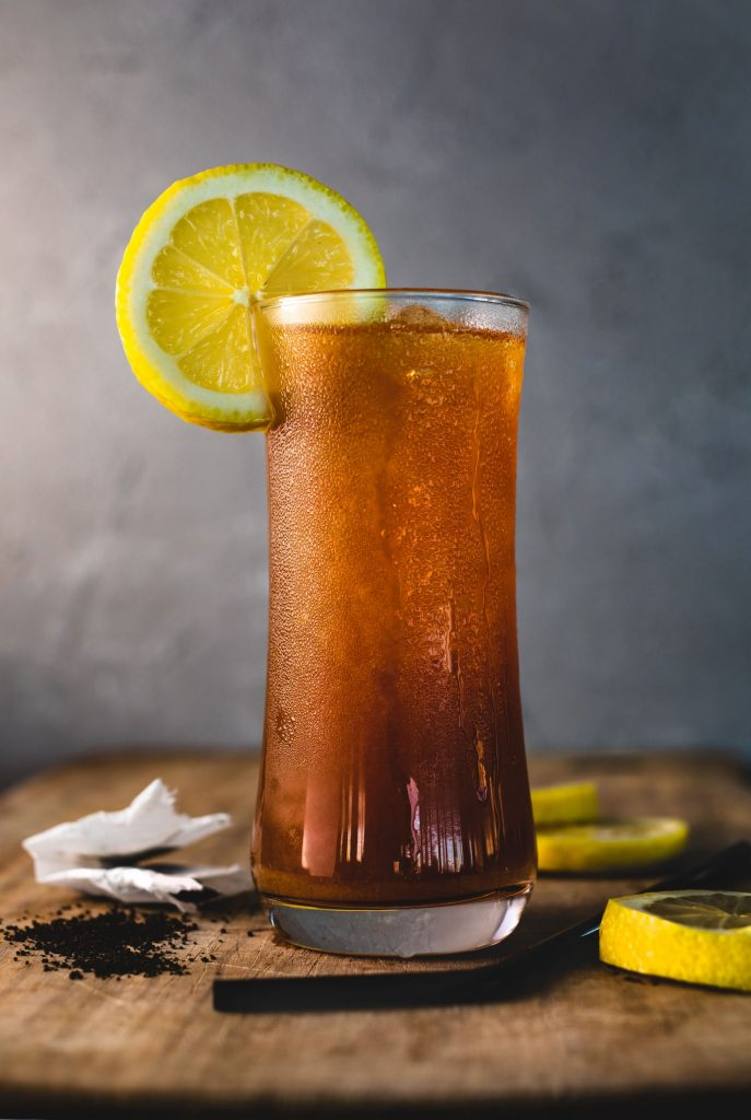 A glass of cold iced tea with a lemon wedge made from loose tea leaves