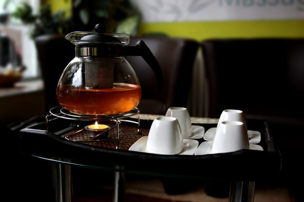 Teapot with infuser placed on top of  a tea warmer