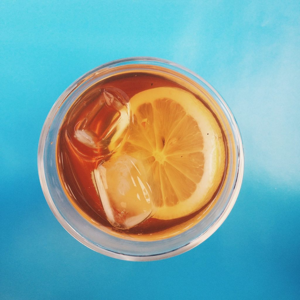 A cup of tea with lemon wedges and ice