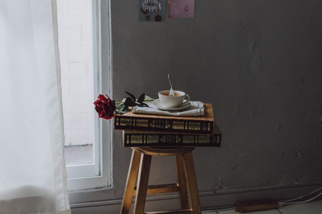 A tea-filled cup on a stack of books placed on a stool