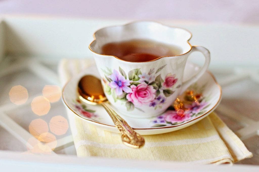 A cup with a floral design filled with tea
