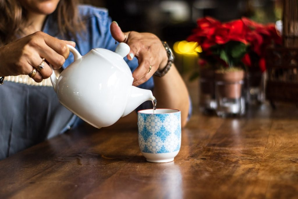 Woman pouring hot water on cup