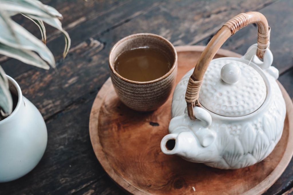 White ceramic teapot and a cup on a wooden tray