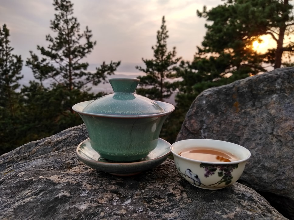 A bowl and a cup of tea placed on top of a rock