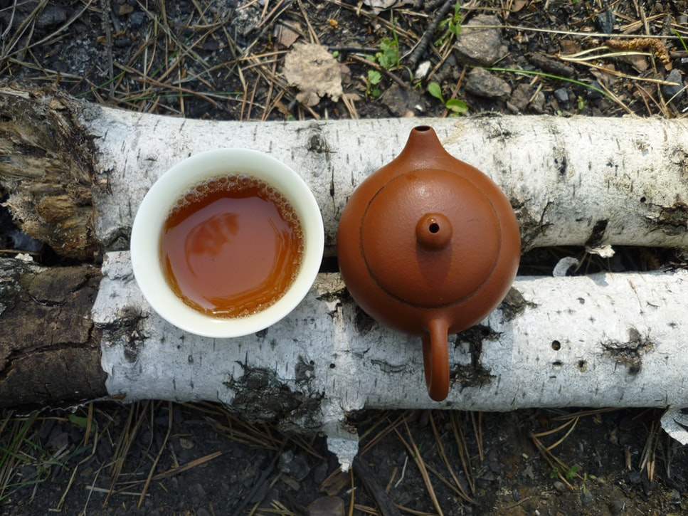 A yixing teapot and a teacup placed on two parallel pieces of wood