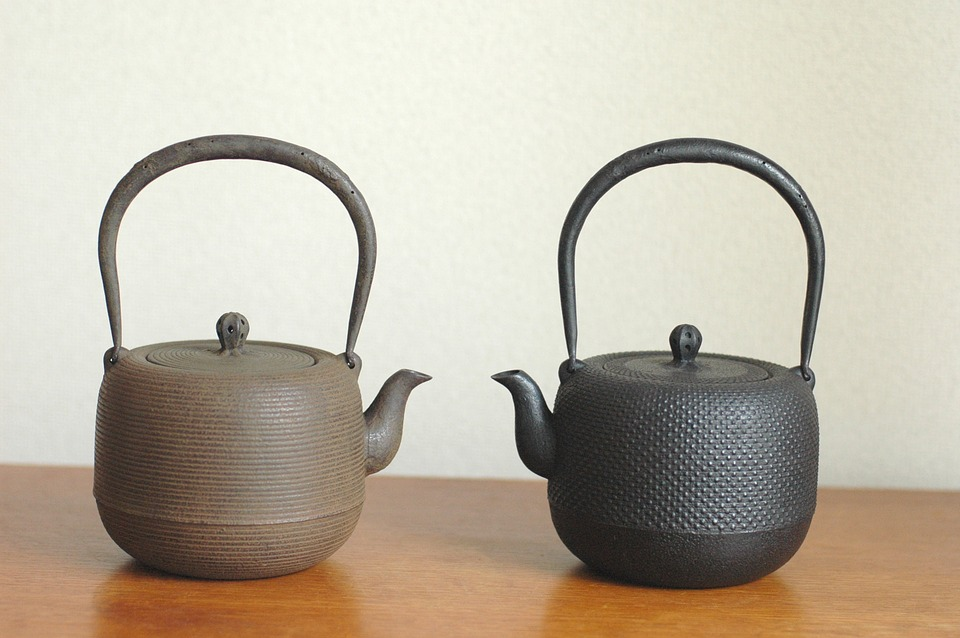 Brown and black cast iron tea kettles