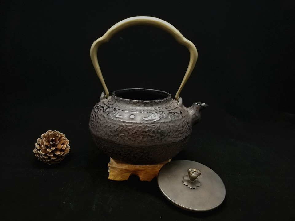 A classic cast iron tea kettle with lid open