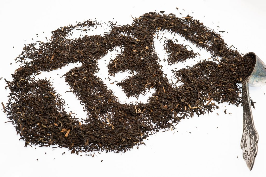 Loose tea leaves scattered on a table by a scoop spelling the word tea