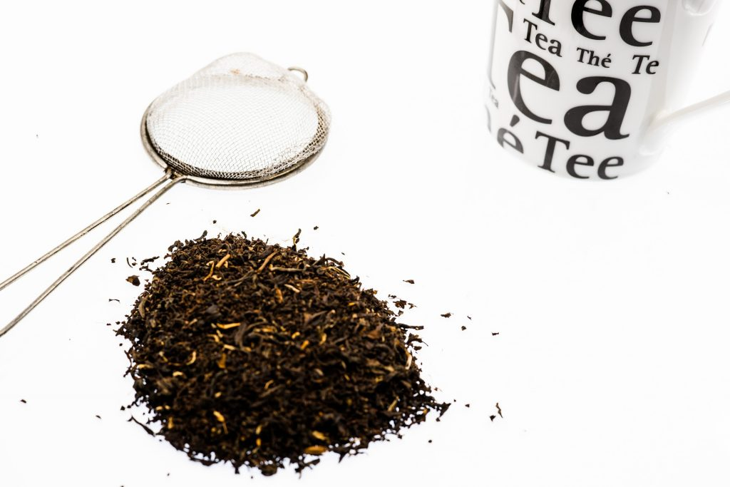 Loose tea leaves on a table with a strainer and a tea mug around it