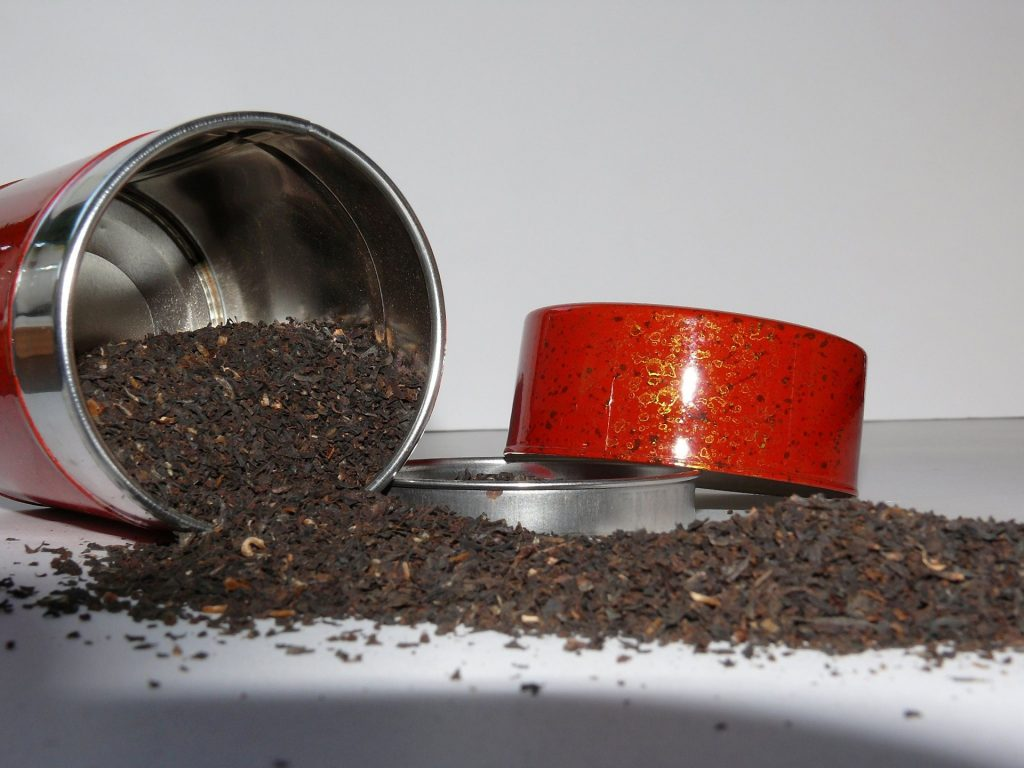 Loose tea leaves spilling out of a red tea container