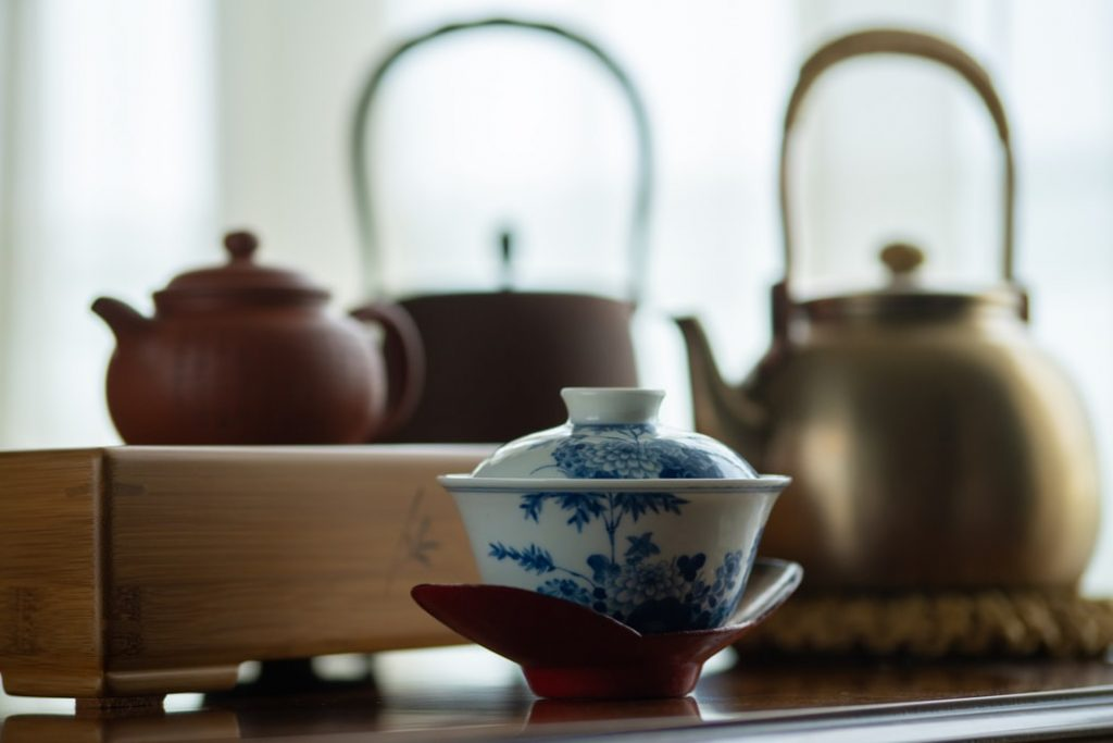 Teapot and tea kettles behind a covered teacup