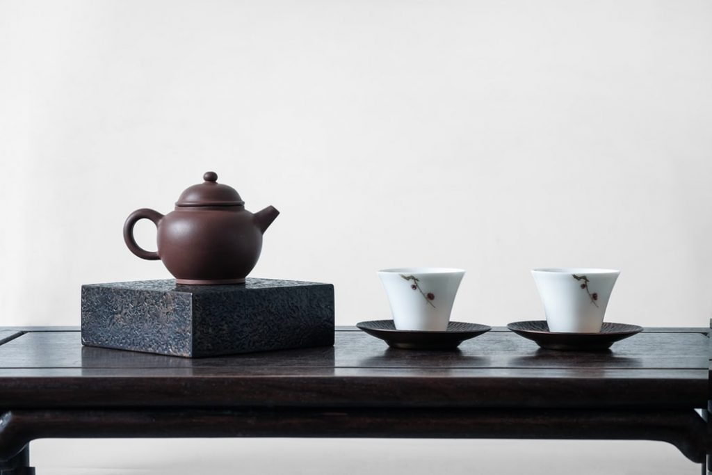 A yixing teapot on a platform beside two cups on saucers