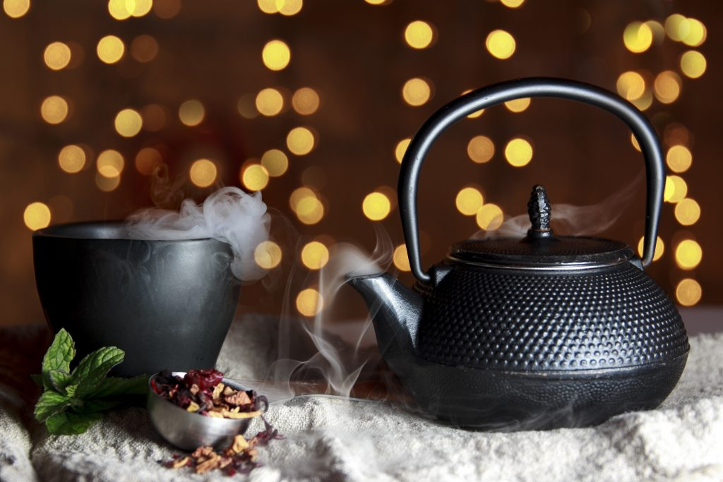 Cast iron teapot fresh from brewing tea as both the teapot and cup emits smoke from the freshly brewed tea