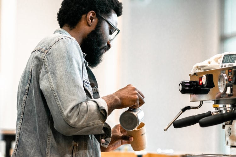 Man pouring milk over his cup after using a coffee maker