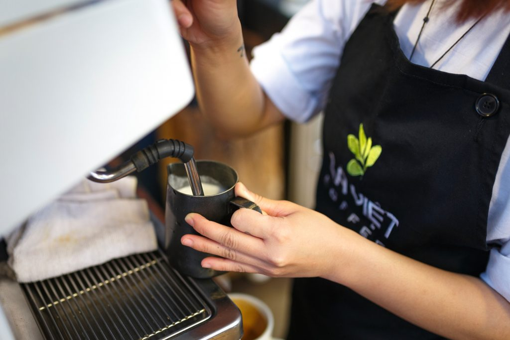Barista frothing milk in a cafe