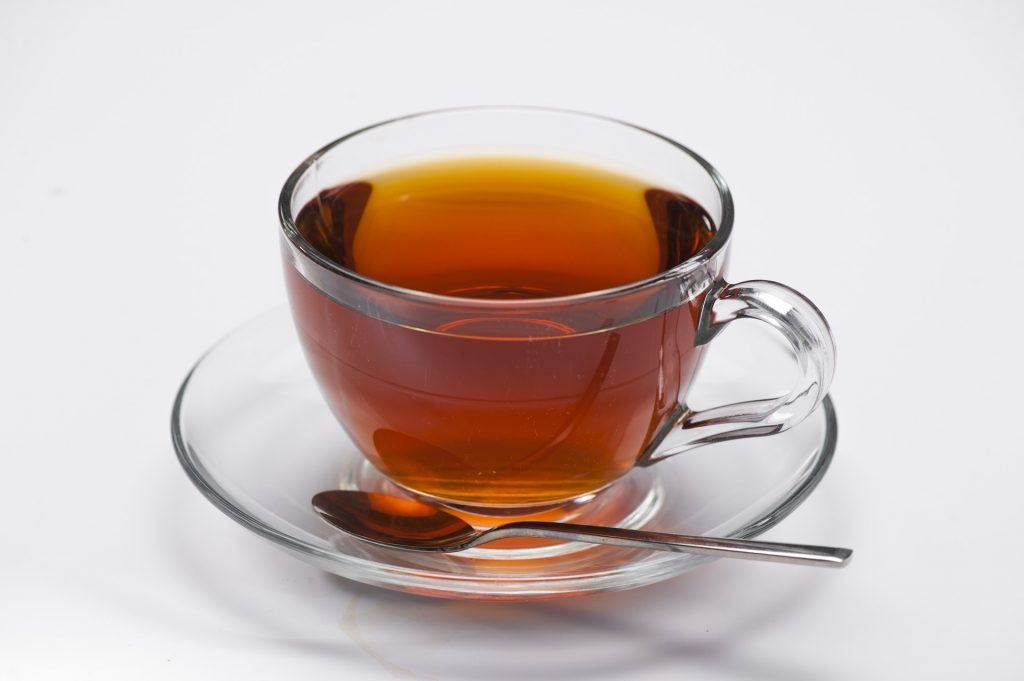 A cup of black tea with a teaspoon and a saucer