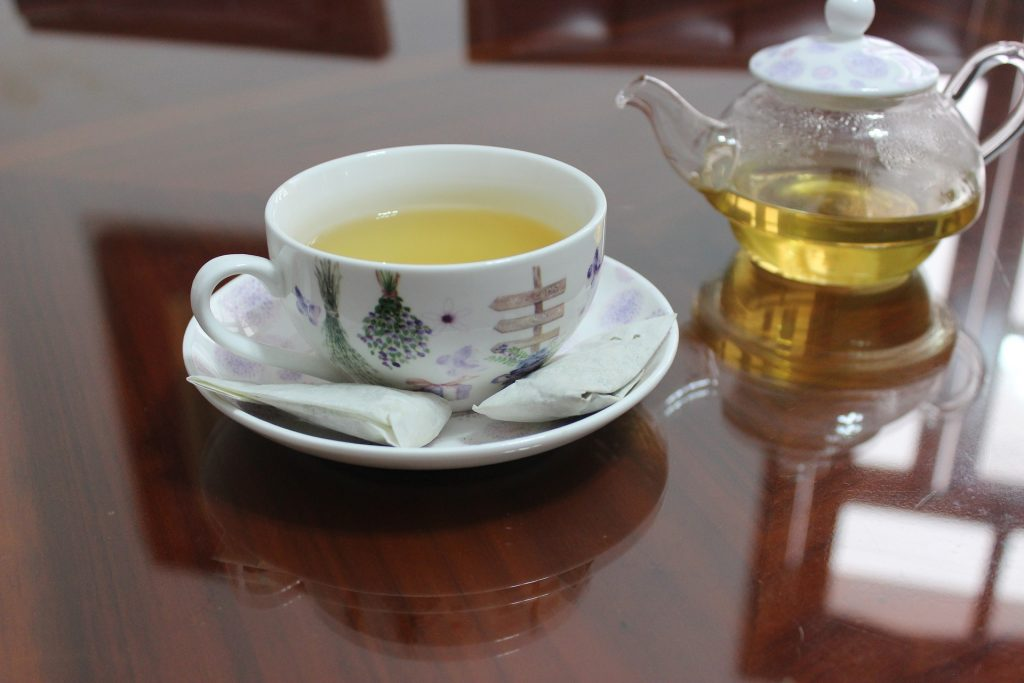 A cup of white tea with two teabags beside it and a tea filled teapot