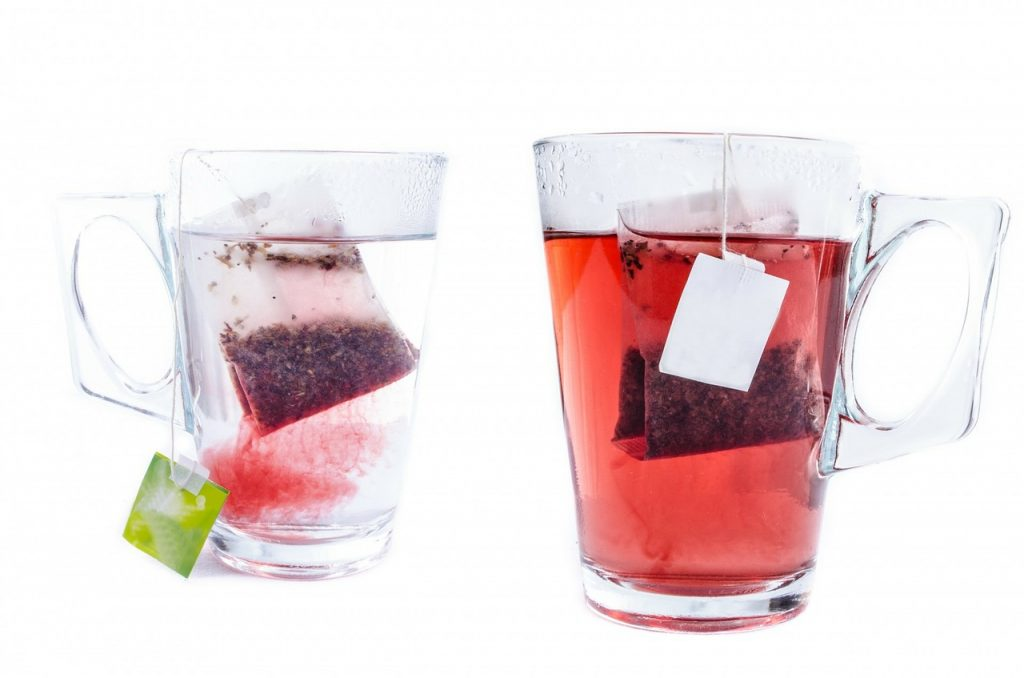 Two cups filled with hot water with tea bags steeping on both of them