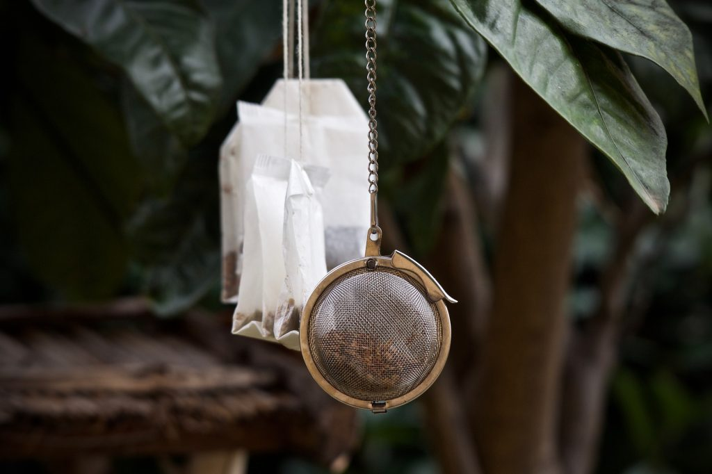 Several teabags and a tea ball infuser hanging mid air