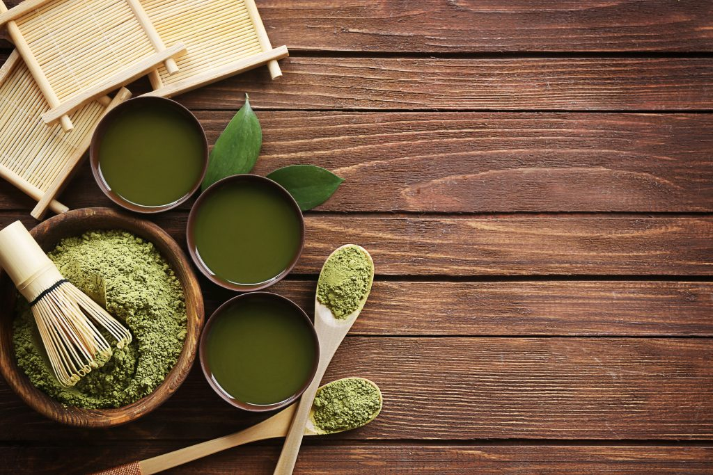 Three cups of brewed matcha tea surrounding a bowl of matcha tea powder with a whisk