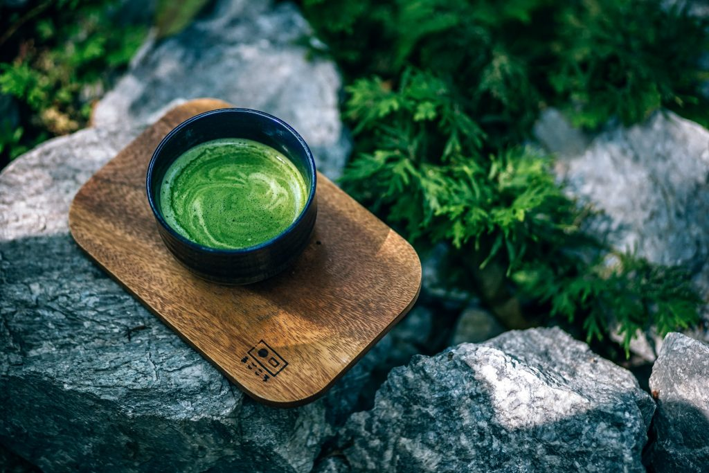 A cup of matcha tea placed in a wooden plank on top of a rock