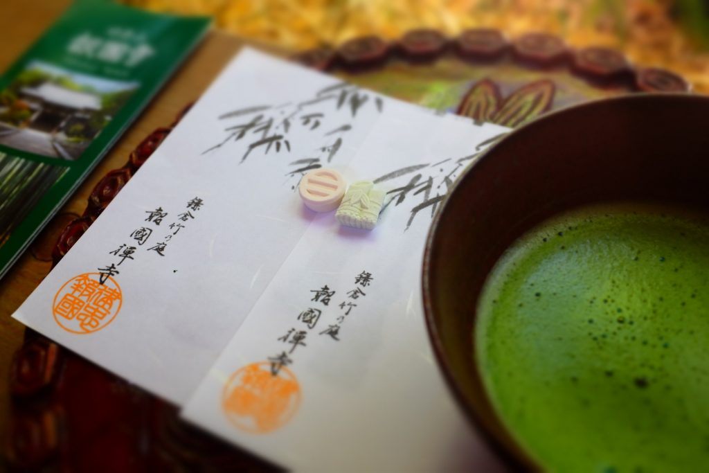 A cup of matcha tea alongside a few welcoming items for a guest