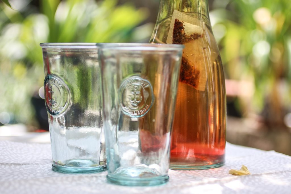 Tea in a glass container with two glass bottles