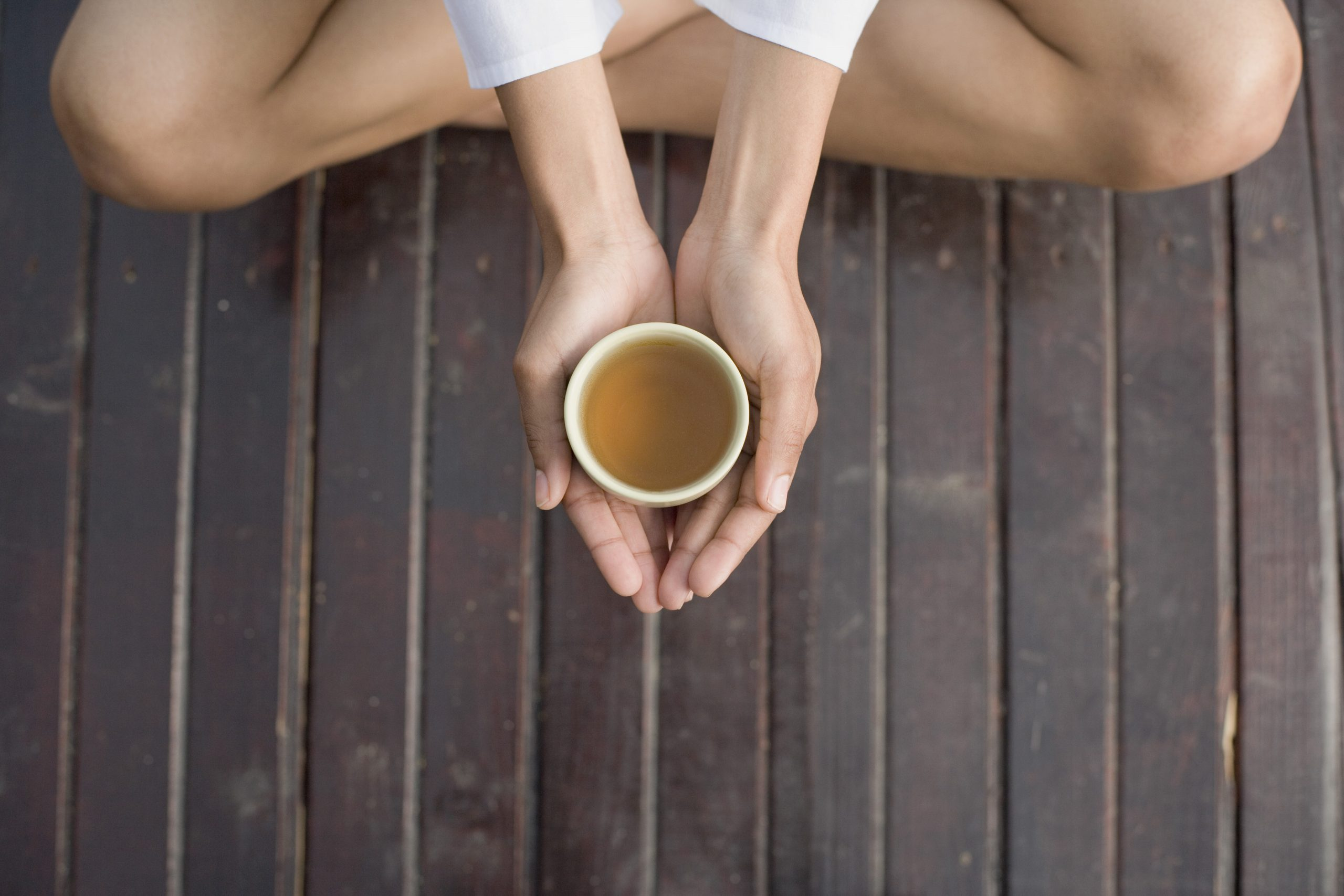 Person holding a cup of tea, wondering does tea have to be refrigerated